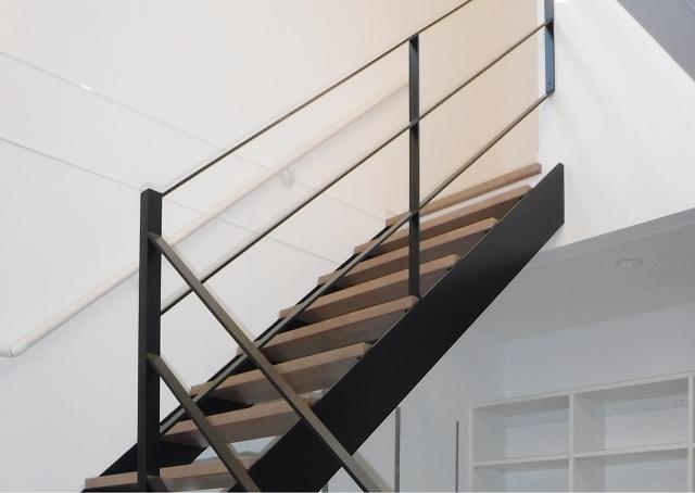 木製の踏み板にアイアン系の手すりのスケルトン階段